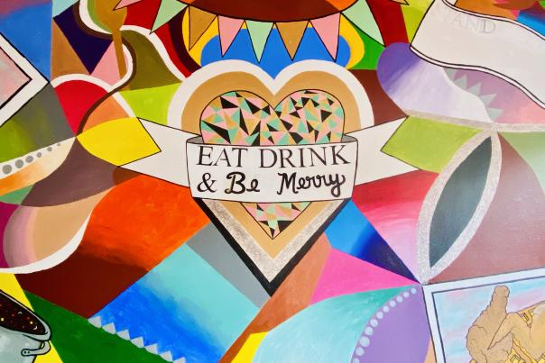 "The colorful mural at Stir It Up advises patron to ""Eat, Drink, & Be Merry."""