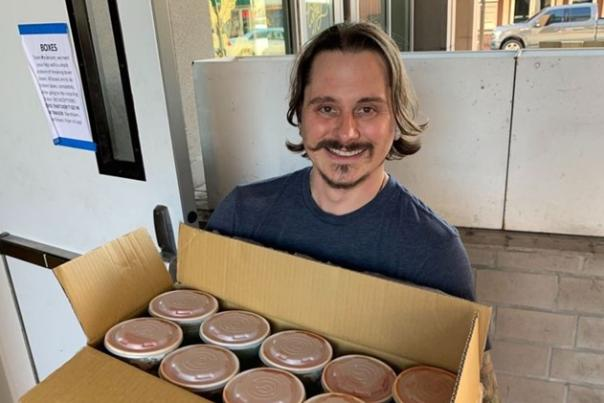 Chef Matthew Cooper of Preacher's Son holds canned goods for relief network