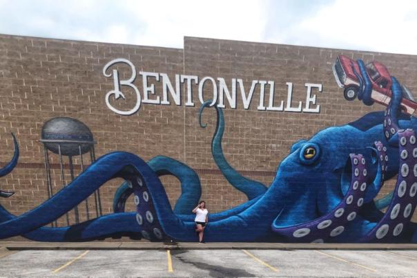 A women standing next to a brick wall. A mural encompases the wall with a huge octopus holding Sam Walton's truck, a bicycler riding up a tentacle, and the Bentonville water tower in the background