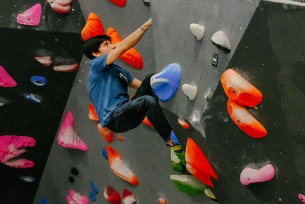 Image of a young boy climbing on an indoor rock climbing wall