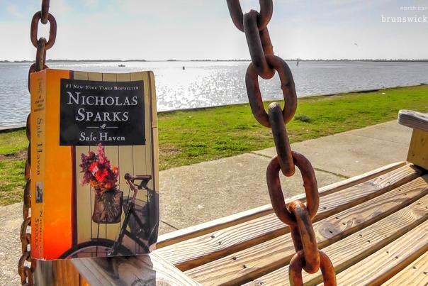 "A paperback copy of ""Safe Haven"" by Nicholas Sparks sits on a swinging bench on the Southport, NC waterfront"