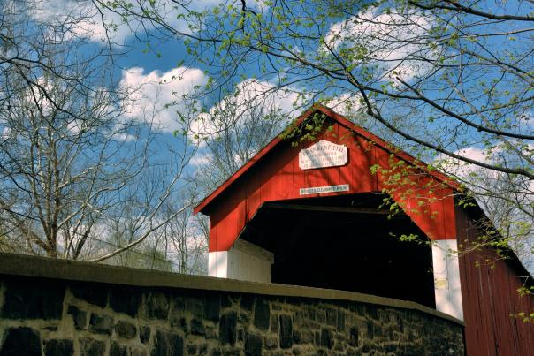 The bright red paint of Frankenfield Covered Bridge shines bright among the greens on a spring day. The bridge is one of 12 remaining covered bridges in Bucks County.
