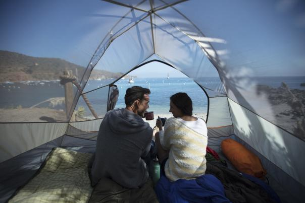 Couple sitting in a tent overlooking the ocean from Two Harbors on Catalina Island