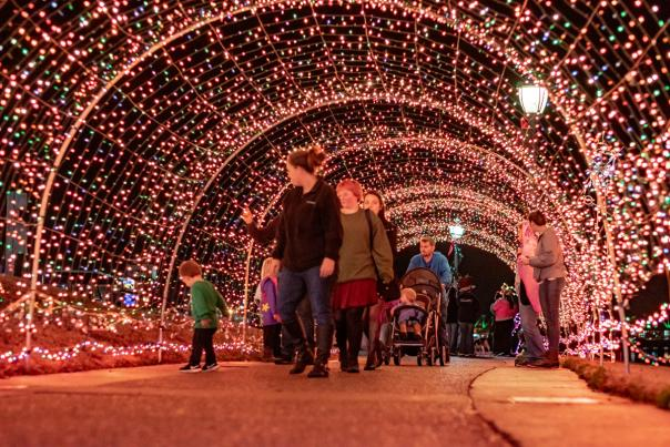 People walking through a light tunnel along the Riverwalk