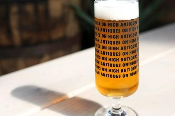 Pint of beer in glass printed with repetitions of Antiques On High's logo