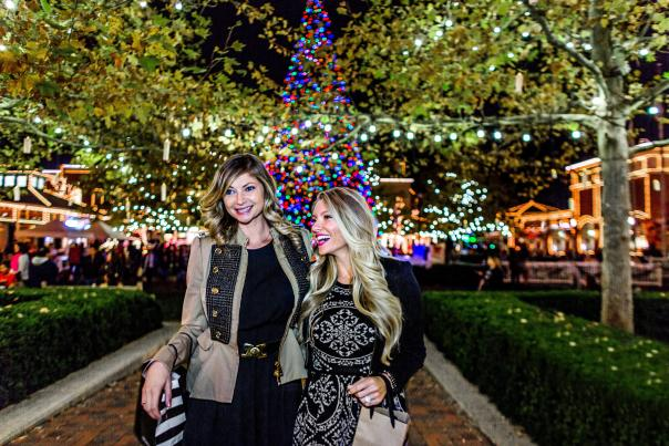 Two women laughing and shopping, walking outside surrounded by holiday lights at Easton Town Center