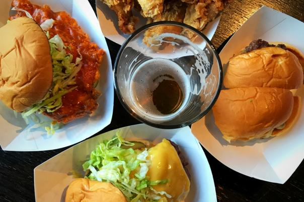 Bird's-eye view of burgers, sandwiches and fried chicken from Preston's Burgers surrounding pint of beer