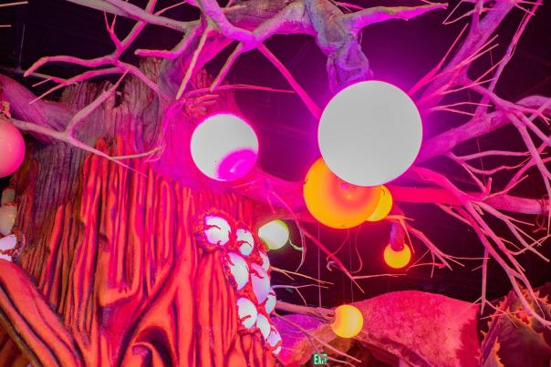 View of colorful artistic tree sculpture adorned with LED orbs inside Otherworld exhibit