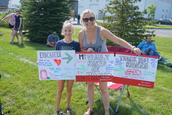 Mom and daughter hold signs for Pelotonia riders