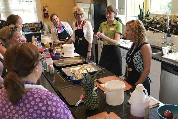 Cooking class in home kitchen with students and teacher surrounding island with various cooking supplies and foods