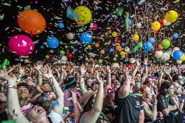 Large crowd at concert celebrating with confetti and balloons falling from ceiling