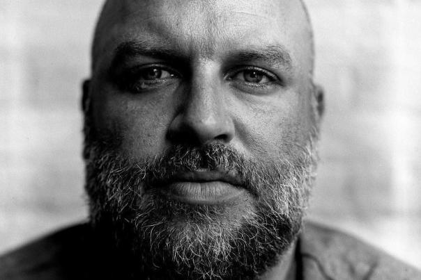 Headshot of Travis Hoewischer, Director of Development at We Amplify Voices