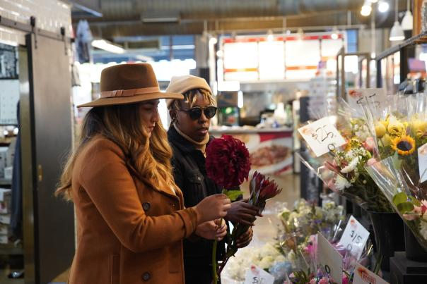 Two people shop for flowers at the North Market