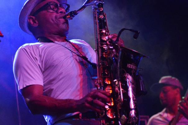 Man playing saxophone on stage with band under vibrant colorful lights.