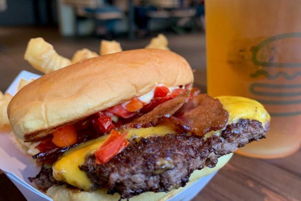 Close-up of burger topped with bacon, cheese, tomato and other toppings in front of glass of beer at Shake Shack