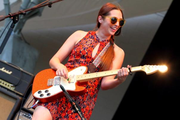 Musician Angela Perley playing guitar and smiling on stage during concert