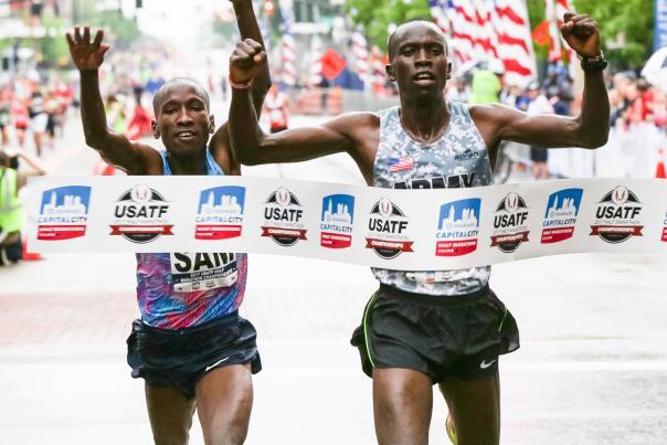 Runners cross the finish line of the Cap City Marathon