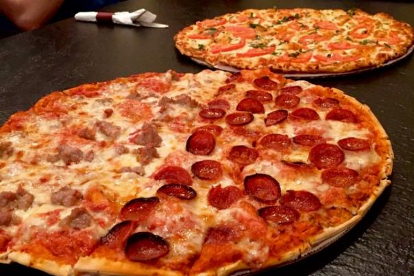 Pizza pies with various toppings at Iacono's Pizza