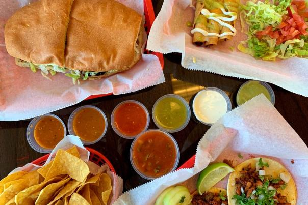 View from above of Latin American sandwich, tacos and nachos on tabletop with cups of various sauces