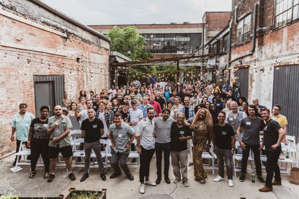 Large group of local musicians and attendees in Strongwater's outdoor courtyard at the Columbus Music Commission's Music Business Mondays forum series