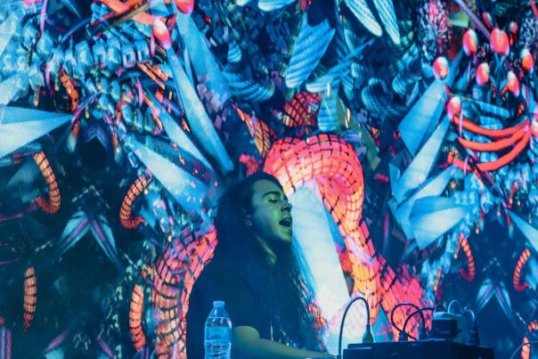 DJ Shatter performing at turntables in front of screen projections of colorful, psychedelic fractals