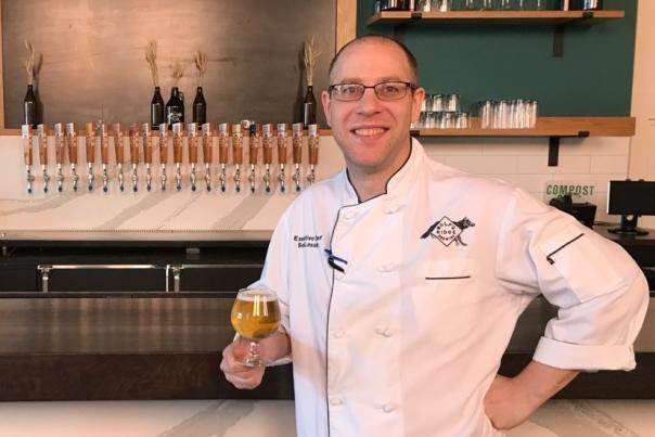 Chef Seth Lassak of Wolf's Ridge Brewing in chef's coat standing at bar holding craft beer