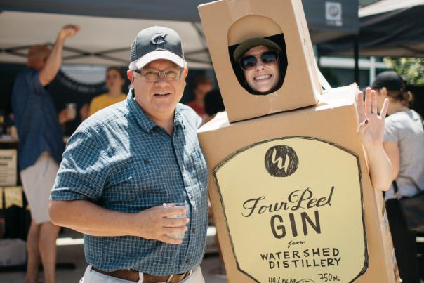 Man poses with a person dressed up as Four Peel Gin