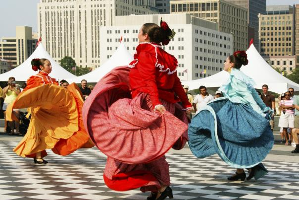 Women dancing in traditional, colorful dresses on stage in front of skyline at Festival Latino