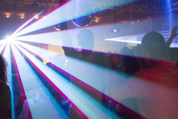 Artistic shot of bright laser lights beaming over dance floor full of people
