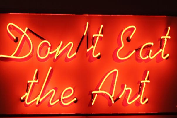 "Neon sign in cursive red lettering that reads ""Don't Eat the Art"""