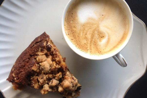 Top-down shot of scone on plate next to mug of foamy coffee from Bexley Coffee Shop