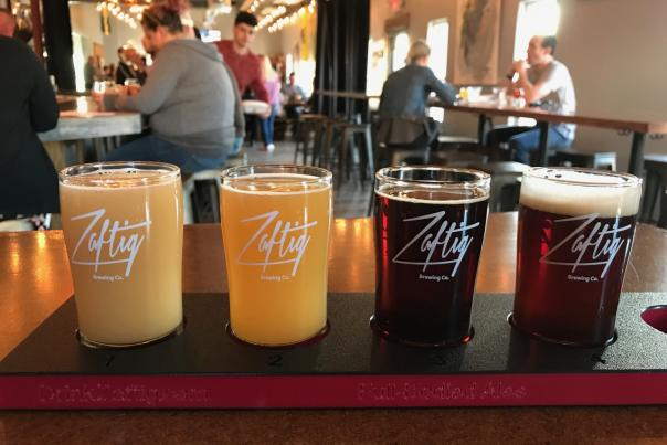 Flight of four different beers in glasses with Zaftig Brewing's logo. Taproom in background with people sitting at tables.