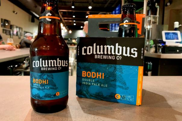 Bottle next to 6-pack of Columbus Brewing Company's Bodhi IPA on countertop of CBC Taproom