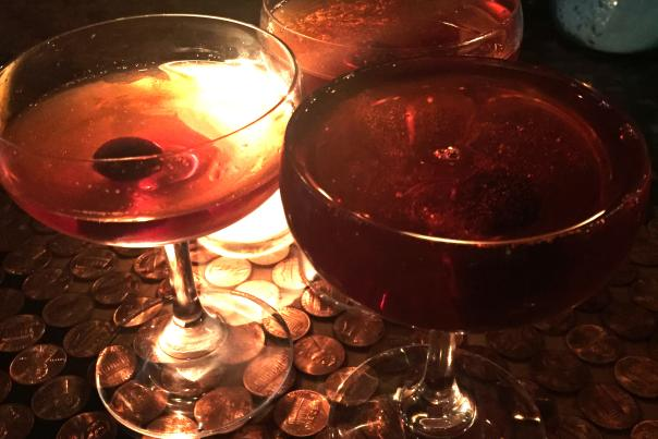 3 Cocktails On A Table With Pennies Under The Glass