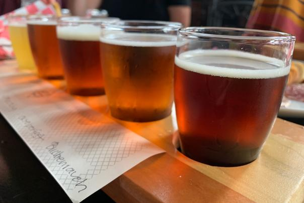 Close-up of flight of various beers on wooden serving plate