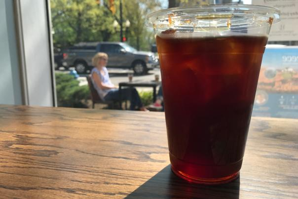 Cup of iced coffee on wooden table in front of window with view of outdoor patio on a sunny day