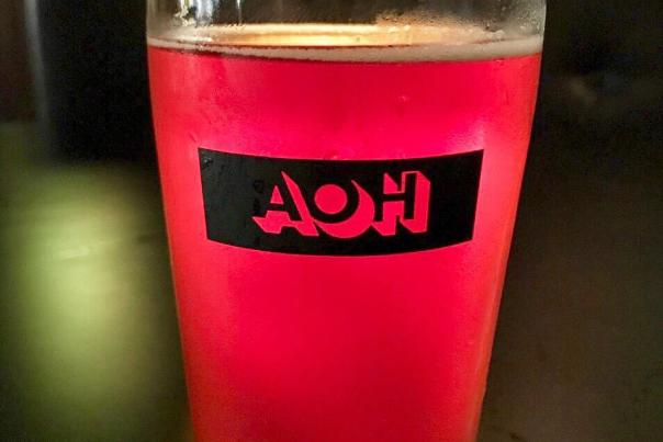 Pint glass of rich, red-colored sour beer at Antiques On High brewery