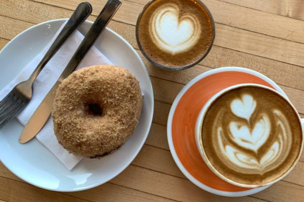 View from above of donut on plate next to two cups of coffee topped with artful foam designs at Roosevelt Coffeehouse