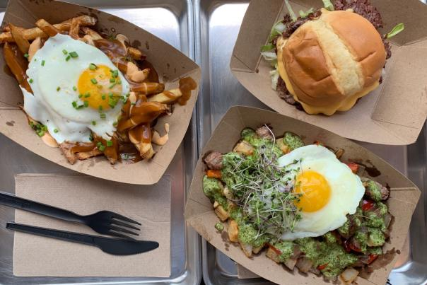 View from above of delicious-looking breakfast food like egg-topped poutine and a sandwich from Short & Stout restaurant
