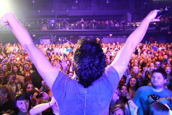 Musician with arms open facing large crowd of fans during concert
