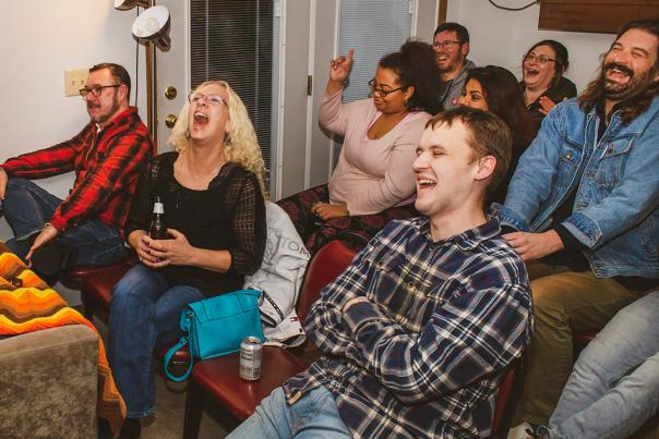 Seated audience in small, intimate space with laughing and smiling faces during a Lampshade Media comedy performance
