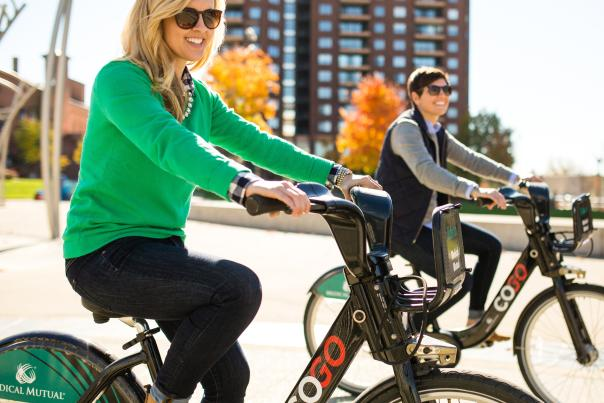 Two women smiling and riding CoGo Bikes in the Scioto Mile area