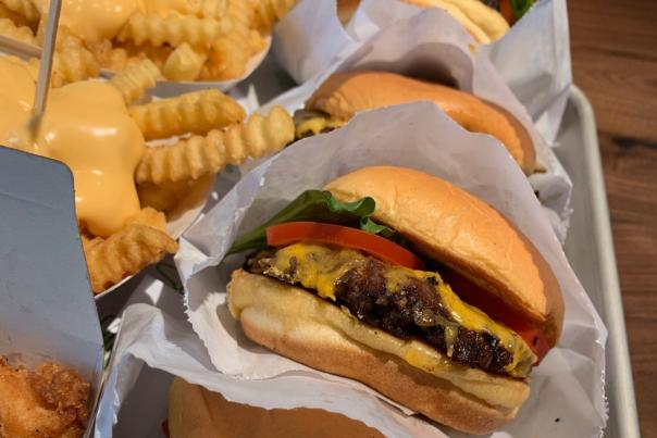 Stack of cheeseburgers and cheese fries from Shake Shack