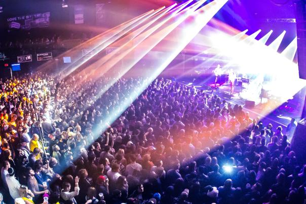 Concert with stage and bright, colorful stage lighting shining on large crowded audience