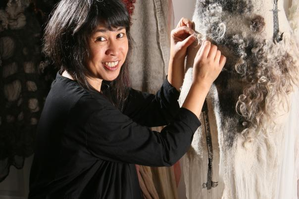 Designer Celeste Malvar-Stewart works on a dress made of sustainable fabrics