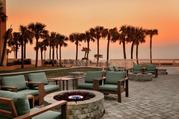 An inviting cozy atmosphere at an oceanfront hotel with soft seating and fire pits