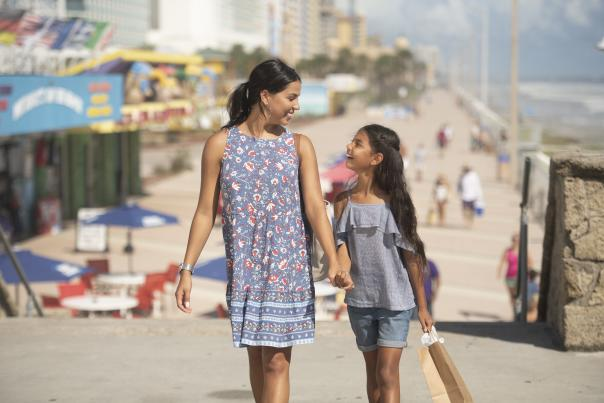 A mother and daughter walk hand and hand along the Daytona Beach Boardwalk.