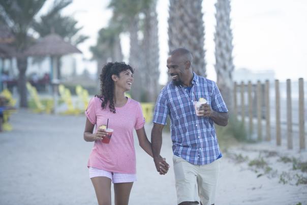 A couple walks hand in hand on the beach.