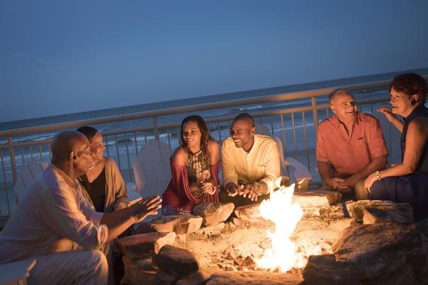A group of friends enjoy the fire pit at an oceanfront beach bar in Daytona Beach
