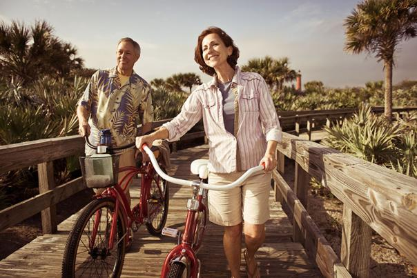 Couples enjoy bicycling on the beach
